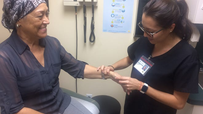 Breast cancer survivor Luz Gonzalez is examined by Tatiana Hooper, MA.