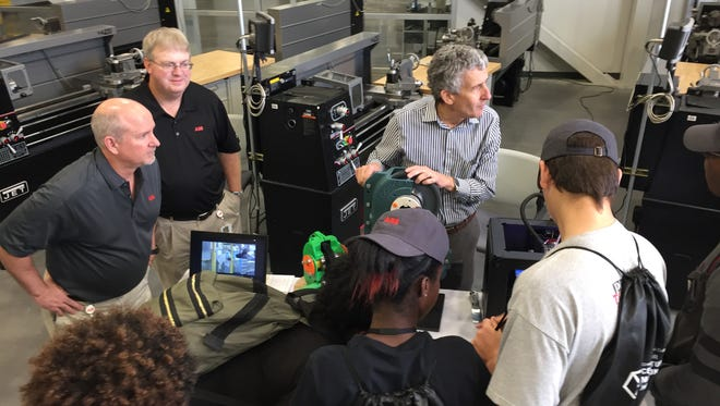 From left, Larry Millwood, Roy Patterson and Patrick Clare describe their company, industrial gear-maker ABB, to a group of students from Wade Hampton High School who toured Greenville Tech's Center for Innovative Manufacturing on Friday and are interested in a career in manufacturing.