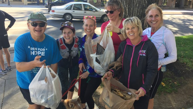 Fort Collins Running Club members hold trash they picked up while running in Fort Collins.