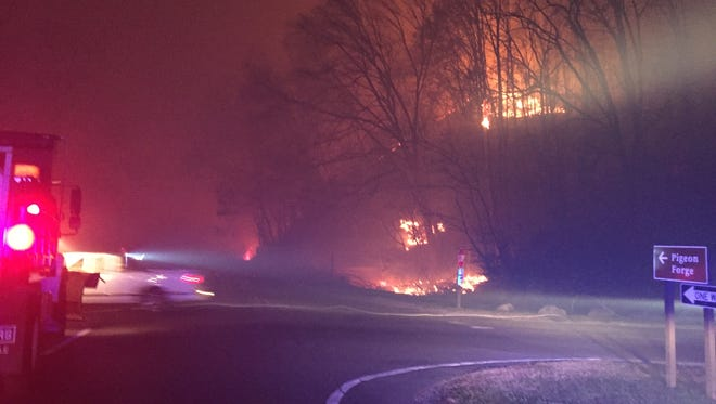 A vehicle with a snow plow is seen approaching the Spur during the Nov. 28, 2016, fires. Such a vehicle was used to help clear trees from the road that evening.