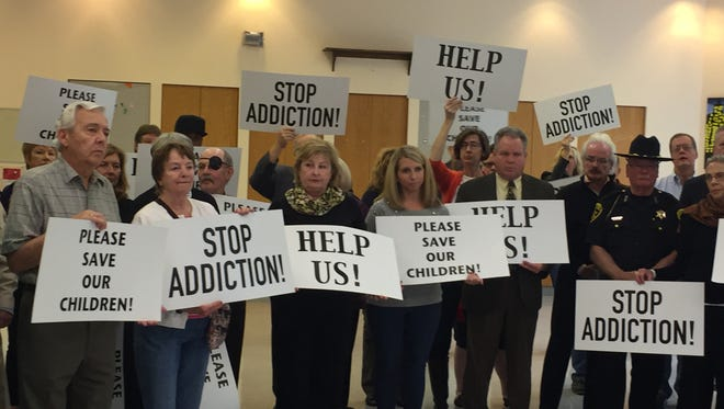 People hold signs against addiction, as officials announce drug treatment services coming at Broome Developmental Center.