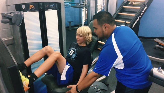 Omar Caponpon, Y Fitness Center Associate, explains fitness equipment to a seventh-grade student.