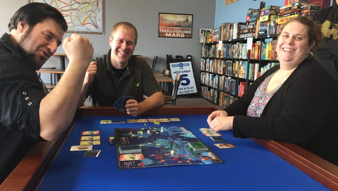 "Crepes and Games owners Jason Rivas (center) and Lynn Rivas (right) play board game ""Pandemic"" Monday Oct. 16, 2017 with classic-video gamer turned board game fan Bryan Buohana (left) at their new board game cafe, which will open in Genoa Township in October."