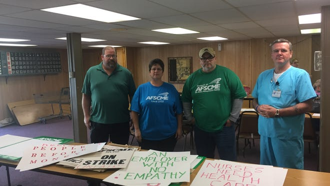 Council director Steve Mullen (left) and Cedar Haven nurses who are leaders in AFSCME Local 2732 display posters Monday that they made last year in preparation for a strike. They are currently making more in anticipation of a strike on Friday.