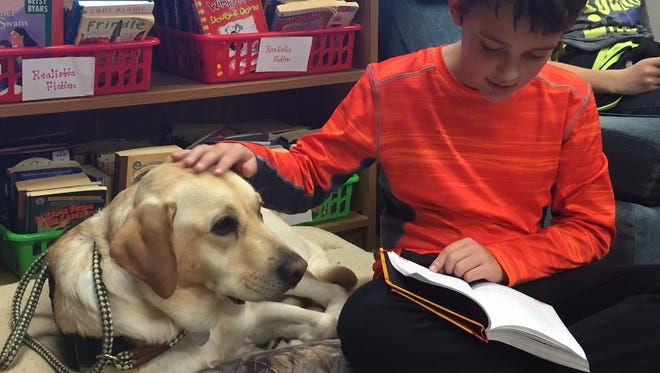 Lucas Lamberjack, a fifth grader, reads and pets Duncan, a 1-year-old Labrador retriever, on Monday, Oct. 18, 2017 at Maltby Intermediate School in Brighton every day.