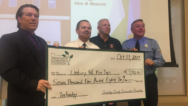The Sandusky County Communities Foundation presented grants to 12 different community organizations on Tuesday. Chairman Tom Bowlus, left, holds with an oversized check presented to the Lindsey Volunteer Fire Department for $7,482.