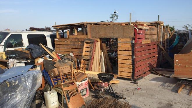 Makeshift pallet structures are seen in a homeless encampment near Ormond Beach.