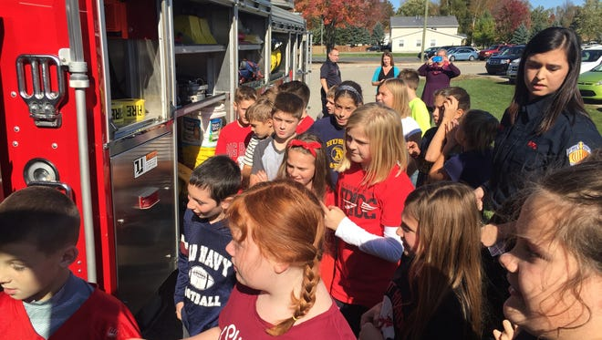 Students at Michigamme Elementary School line up to tour the cab of a firetruck.