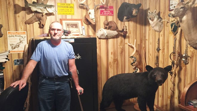 """John Eisenhauer stands in his """"man cave"""" on Grace Avenue in Swatara Township on Nov. 1. A Pennsylvania Game Commissioner confiscated signs from Eisenhauer that were hanging in this room."""