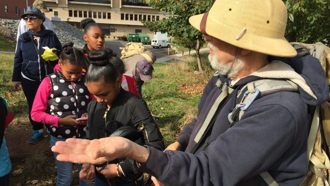 Naturalist Steve Brill holding a handful of foxtail grass seeds picked at William Paterson's campus.