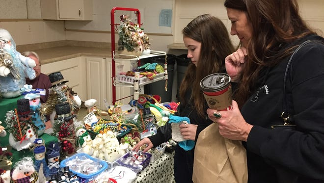 Addy Wolvin, left, and Kim Dortman check out some of the items for sale at the Blue Water Women's League Craft Fair on Saturday, Nov. 4, 2017, at the Marysville American Legion Hall.