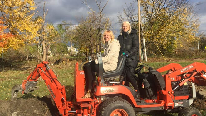 Rev. Faith Fowler (R) and Lori Wingerter of GM sit on a tractor at the groundbreaking for five new tiny homes in Detroit.