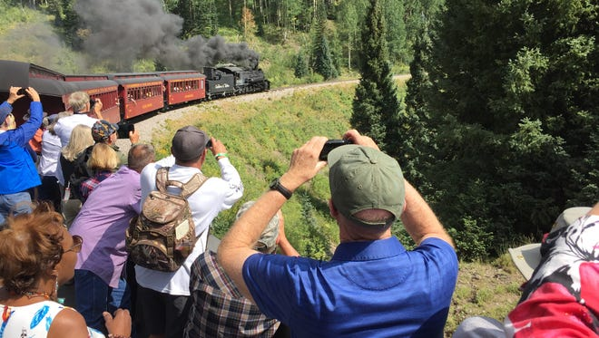 Visitors on an open observation car shoot photos of the steam engine as it rounds a bend during a ride on the Cumbres & Toltec Scenic Railroad. The train takes trips as long as 64 miles through the San Juan Mountains of northern New Mexico and southern Colorado.