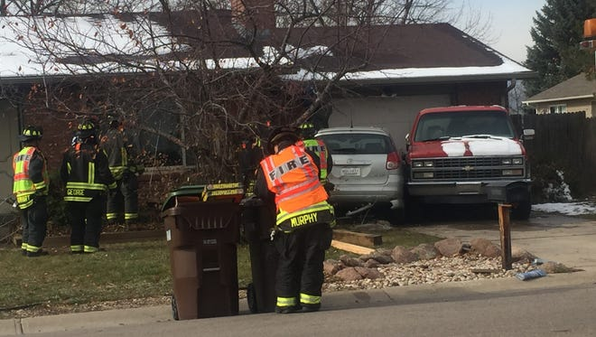 Fire crews check the damage done to a house in south Fort Collins after a car crashed into the side of it.
