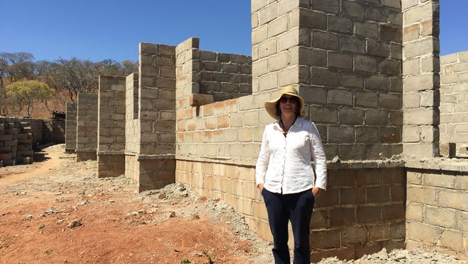 Special-education teacher Melissa Bryant in front of the in-process community library in Chisekesi, Zambia. Her students are helping Zambian students get their education.