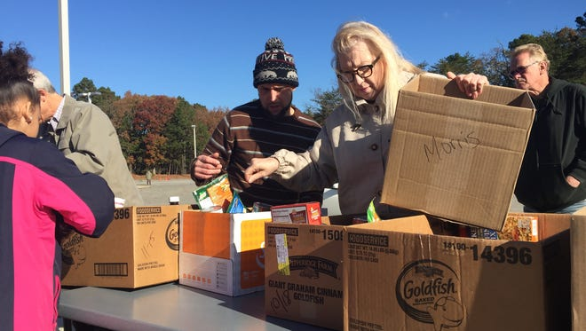 Help & Hope Ministries volunteer Marie Cliff organizes donated food on Thursday outside Holly Heights Elementary School in Millville. The food will go toward proving the makings of Thanksgiving Day dinners.