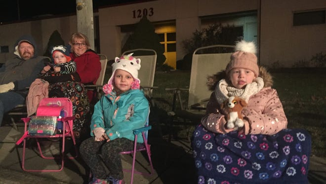 Alyssa Tisa, 6, and Madison Baker, 5, (left and right, foreground) wait for the start of the 2017 Millville Christmas Parade Friday night.