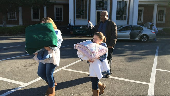 Tallahassee Democrat Senior Writer Byron Dobson shows the way for some of the first donators during a previous Blanket Day drive.This year's event begins at 8 a.m. Dec. 9.