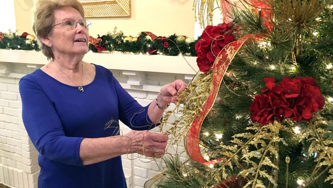 Suzanne Stewart, director of the Deming-Luna-Mimbres Museum, trims a Christmas Tree in preparation for the museum's annual Green Tea fundraising event slated for 1:30 to 4 p.m. on Sunday, Dec. 10.