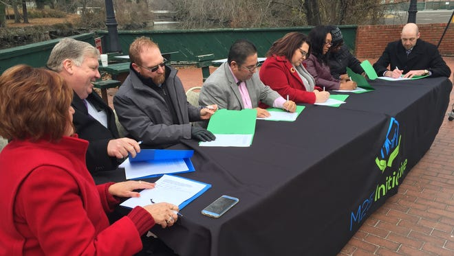 Members of The M25 Initiative's Housing First Collaborative sign a memorandum of understanding that launches a second phase in efforts to placing homeless people in permanent housing. The signing came at a press conference Friday morning in Bridgeton at the waterfront plaza. At far right, is M25 founder and president Robin Weinstein.