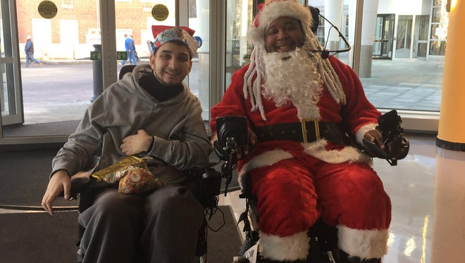 Eric LeGrand and Mike Nichols took several pediatric patients by surprise with a visit at PSE&G Children's Specialized Hospital In New Brunswick Monday. With smiles, laughter, encouraging words and shared experiences, Nichols and LeGrand — who dressed as Santa Claus — easily related to the patients currently facing similar health issues and disabilities.