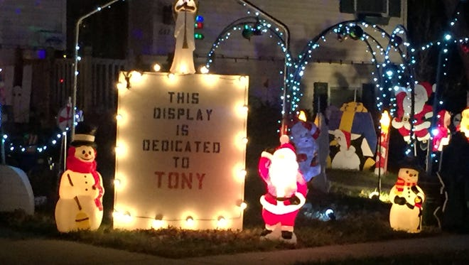A plaque that honors Tony Loffer is a prominent part of a display created by Rich Cobb. The two were neighbors and had a holiday light rivalry going each year.