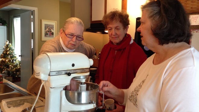 Allison Friedman and Elizabeth Snyder observed carefully as Valerie Derrick mixes the dough for Scottish shortbread cookies. Valerie recently taught them the intricacies of successfully making the special holiday treats.