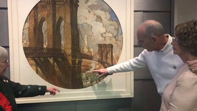 Details in a portrait of the Brooklyn Bridge painted for the 1939 New York World's Fair catch the attention of donors who paid for its restoration and attended its recent unveiling at the Roebling Museum. They are, from left, Mary Elllen Eckman and Ken Ibach and wife Chloe.