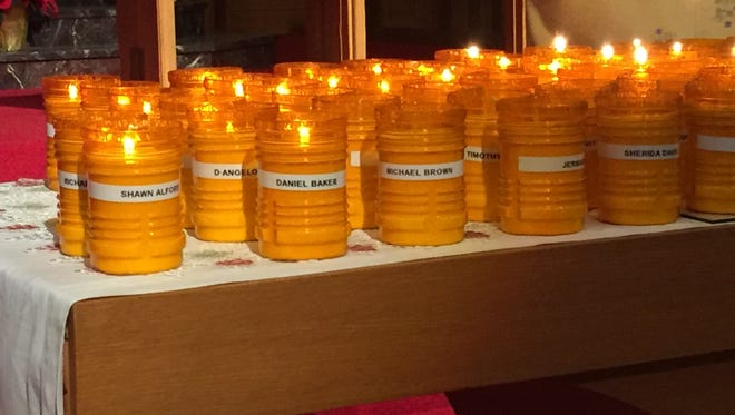 Some of the 128 candles for Milwaukee's 2017 homicide victims burn at a vigil Saturday.