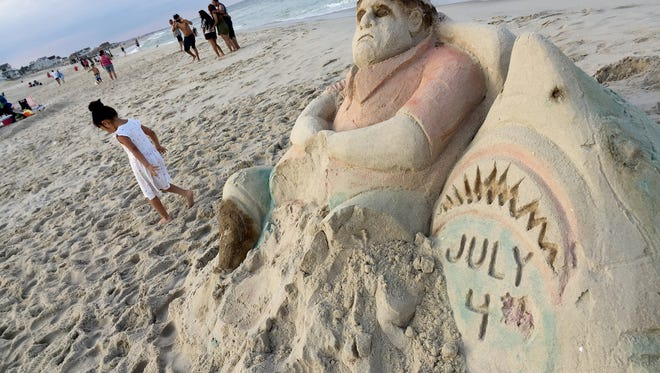 Emily Lopez, 5, West New York, walks past a sand sculpture of NJ Governor Chris Christie on the Seaside Heights beach Tuesday, July 4, 2017.  On the far side of the sculpture is a 'beach closed' inscription.
