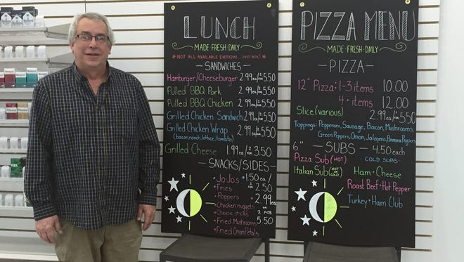 Valero 24 Store manager Chris McBride stands by the menu board at the new business in Shelby.