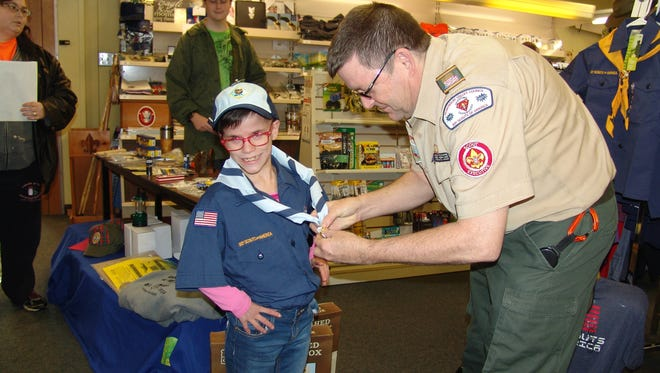 Ed MulHolland adjusts Zoey Girard's new Cub Scout uniform Monday at the Boy Scout Council office in Zanesville.