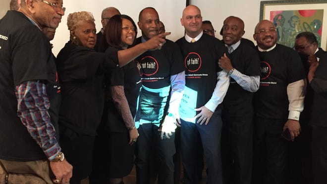 Detroit school officials and local clergy pose for a picture wearing shirts given out during an event Thursday aimed at getting faith-based leaders involved in Detroit schools.