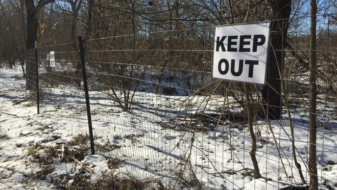 City crews erected a wire fence and Keep Out signs Friday to block off the two dangerous swallow holes in Wilson's Creek from public access.