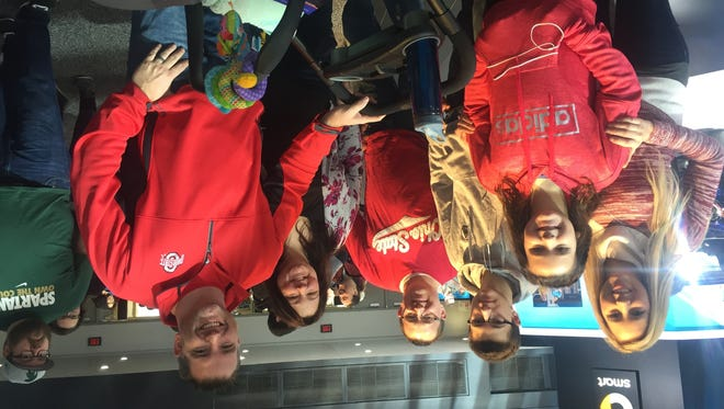 From left to right Buckeye fans Tara Bollinger, Braelynn Bollinger, Caleb Bagi, John Bagi, Greta Bagi and Brian Bollinger from Sylvania, Ohio take in the North American International Auto Show Saturday morning. The little one in the carriage is Garrin Bollinger.
