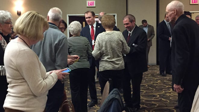 Candidates for state senate district 7 seat Brian Buchanan and Ed Cripe shake hands with precinct committee members before the final vote.