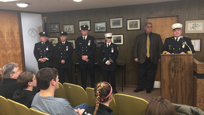 """Millville Fire Chief Michael Lippincott (podium) presented  """"life-saving"""" medals to department members at Tuesday night's City Commission meeting. Present to accept awards (left to right) were Firefighters Kevin Quay, Scott Haley, and Patrick Wettstein and Capt. Christine Tonetta. Firefighters Ryan Gandy was absent."""
