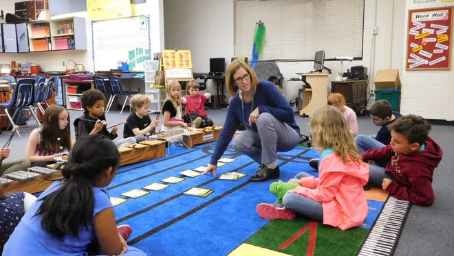Barbara Hartsfield shows students how to use the staff in the center of the music rug.