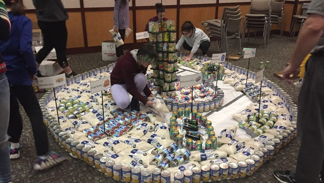 Students from the Logos and Early College Programs build an animal cell out of canned goods for the 2018 Canstruction competition.
