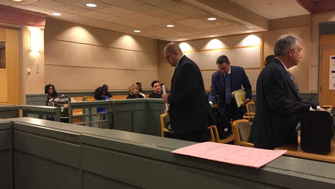 Jeffrey E. Profitt (center, standing) hurries from a Cumberland County Superior Court hearing on Monday. The hearing was to consider whether he will get one or two trials on prisoner abuse and related charges.