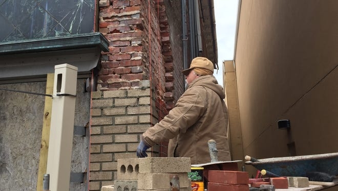 Dave Wartman carries out repairs Monday to a facade corner of the Fath Building at 120-124 N. High Street in Millville. Wartman, who owns Tristate Masonry Restorations in Washington Township, said he is talking to the owner about further restorative work on the exterior.