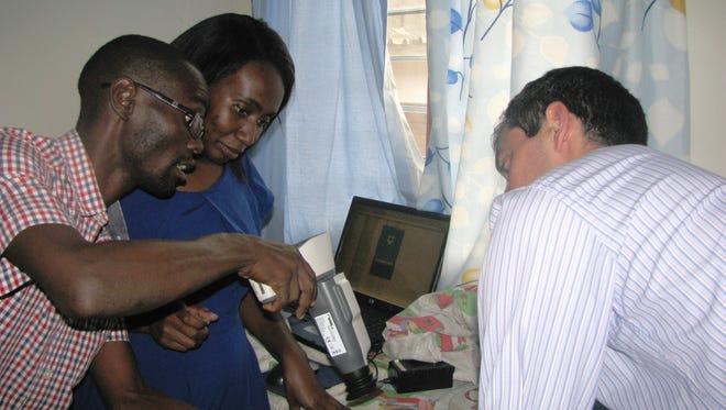 Doctors examine a malaria patient.