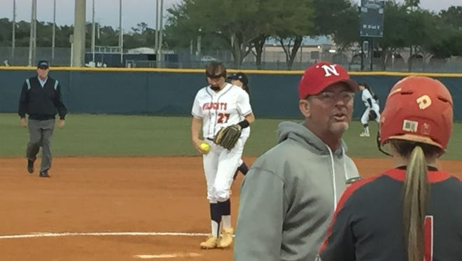 Estero's Alexandra Salter takes over on the mound as North Fort Myers coach Jeff Miner discusses things with on-deck batter Sarah Giompalo during the second inning of Wednesday night's game.