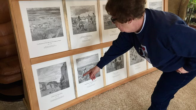 Julie Ameline points out her favorite features in a set of prints donated to the Old Trail Museum wild game feed fundraiser by Havre artist Don Greytak.