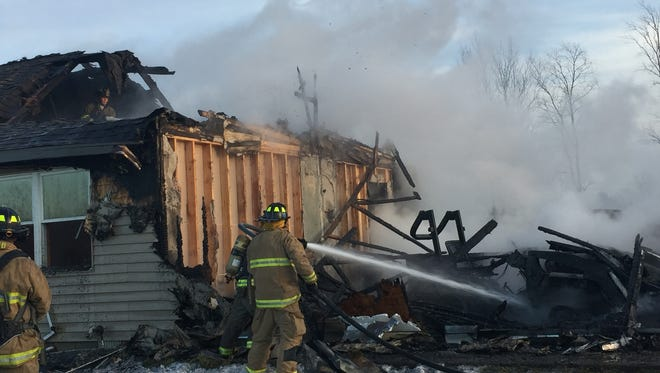 Firefighters extinguish the remains of a fire that destroyed a Marion Township home on Monday night.