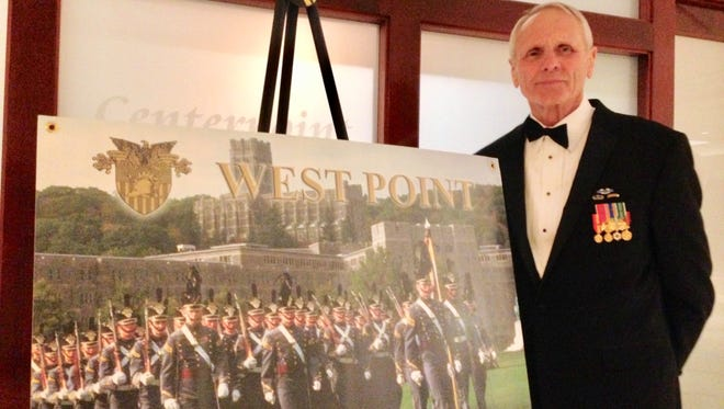 Jim Suhay stands by the West Point poster at the Founders Day celebration of the West Point Society of Michigan. West Point graduates welcomed the 20 young candidates who have been admitted to the class of 2022.