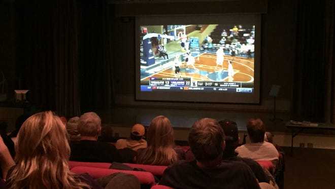 Fans watch the Ashland University women's basketball team on the big screen at the Hawkins-Conard Student Center Auditorium on Wednesday night.