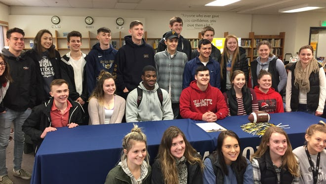Tony Schoenborn (red shirt) is surrounded by friends at his signing ceremony on Thursday, March 22, 2018.
