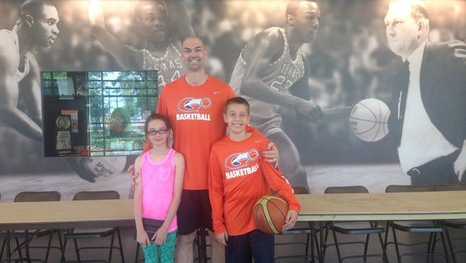 Former UTEP men's basketball player JoJo Garcia poses with his children while visiting UTEP.