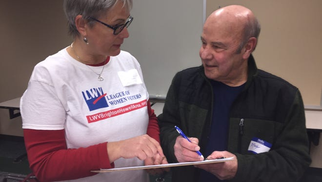 """Terri Wilkerson of Pinckney speaks with Max Manning of Oceola Township about the """"Promote the Vote"""" campaign petition, during a meeting of the League of Women Voters Brighton/Howell area unit, at the Brighton Library on March 26, 2018."""